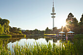 People sitting on the terrace of the Seepavillon snack bar at the park lake, television tower in the background, Planten un Blomen, Hamburg, Germany