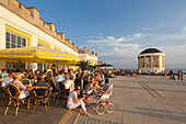 People sitting in a cafe on the beach promenade, Pavilion in the background, Borkum, Ostfriesland, Lower Saxony, Germany
