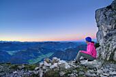 Woman sitting for a rest on the Nurracher Hoehenweg with view to Hohe Tauern range, Nurracher Hoehenweg, Loferer Steinberge range, Tyrol, Austria
