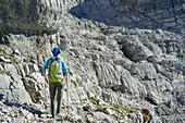 Woman hiking on karst formation, Nurracher Hoehenweg, Loferer Steinberge range, Tyrol, Austria