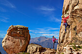 Man climbing on red Granite rock is being belayed by woman, Mottarone, Piedmont, Italy