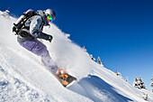 Woman downhill snowboarding, free ride skiing area Haldigrat, Niederrickenbach, Oberdorf, Canton of Nidwalden, Switzerland