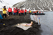 Tourists bathing in the hot springs of the crater lake of Deception Island, South Shetland Islands, Antarctica
