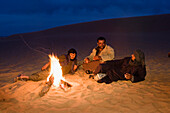 beduins warming at campfire, Akakus mountains, Libya, Africa