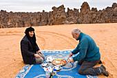 Tuareg and tourist eating, Tassili Maridet, Libya, Africa