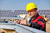 Bauarbeiten auf dem Solarpark am Peterswald, Bauarbeiter mit Helm bei der Arbeit, Neuental, Hessen, Deutschland, Europa