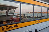 Vaporetto waterbus, floating jetty, mooring, pontoon,  approdo, reflection of water and gondola, Venice, Italy