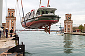 Vaporetto, water bus, public transport, lowered by crane at maintenance docks, hoisted, Arsenale, Venice, lagoon, Italy