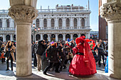 Venetian Carnival, tourism, masks, red dress, costume, posing, army of  photographers, arcade of Doge Palace, San Marco, Venice, Italy