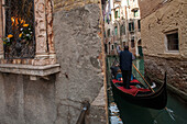 tourist trip on gondola in a narrow canal in historic Castello, rowing gondolier, shrine of the Virgin Mary, romantic, old walls, Venice, Veneto, Italy