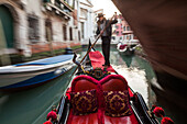 tourist trip on gondola in a narrow canal in historic Castello, art of rowing, gondolier, below bridge in narrow canal romantic, blurred, moving, Venice, Veneto, Italy