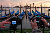 gondolas in evening light moored at San Marco, paline, digital tourist cameras on Tripod, symbolic image, background San Giorgio Maggiore, Venice, Veneto, Italy