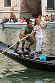 father teaches daughter standup rowing in venetian gondola, Canal Grande, Veneto, Venice, Italy