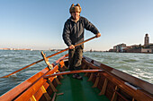 rowing teacher Giorgio, rowing a traditional Sandolo boat in the lagoon, Veneto, Venice, Italy