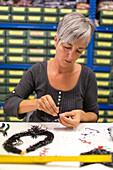 glass bead artist in studio of Luisa Conventi, Atelier Gioia, threading beads, jewellery, Venice, Italy