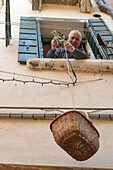 senior citizen lowers basket from upstairs, down to collect his mail from the post delivery, curiosity, Venice, Italy
