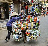 vendor pushes her load through the streets in Hanoi, Vietnam.