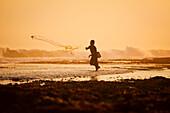Indonesia, Bali, Uluwatu, Fisherman Throwing Nets At Sunset, Waves Crashing In Background