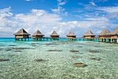 French Polynesia, Tuamotu Islands, Rangiroa Atoll, Luxury Resort Bungalows Over Ocean.