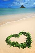 Hawaii, Oahu, Kualoa, Heart Shaped Maile Lei On The Beach With Chinamans Hat In Background