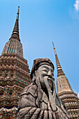 'Stone guard statue and temple spires (chedi) at Wat Pho, the Temple of the Reclining Buddha, the largest Buddhist temple in Bangkok; Bangkok, Thailand'
