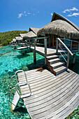 French Polynesia, Moorea, Luxury Resort Bungalows Over Ocean.