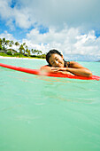 Hawaii, Oahu, Lanikai, Young Japanese Woman Lying On Surfboard In The Ocean.