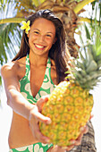 Teenage Girl Wearing A Bikini Holding Out A Pineapple, Flower In Her Hair, Palm Tree In Background.