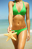 Girl Standing On Tropical Beach Holding Out A Starfish, Legs And Torso