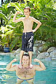 Boy Standing On His Father's Shoulders In Pool