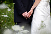 Wedding Couple Holding Hands In Field Of Wild Flowers