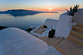 View From The Village Of Oia Perched On Steep Cliffs Overlooking The Submerged Caldera At Sunset, Santorini, Greece