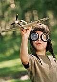'Fv2070, Natural Moments Photography; Young Boy With Aviator Goggles And Hat Playing With A Toy Plane'