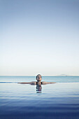 Woman Relaxing In Infinity Pool, Panama City, Panama