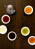 Teapot And Different Types Of Tea In Cups On A Wood Table