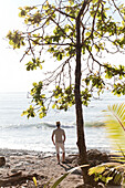 'Man Stands Under A Tree Watching The Surf; Matapalo, Costa Rica'
