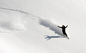 A Snowboarder Throws Up His Arms In Celebration While Snowboarding In Turnagain Pass Backcountry, Southcentral, Alaska