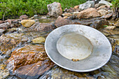 Gold Pan With Gold Nuggets Sits On Rocks In A Stream At Hatcher Pass In The Talkeetna Mountains Of Alaska During Summer.