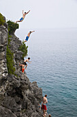 'Men leaping from a cliff into turquoise water of Georgian Bay in Bruce Peninsula National Park; Ontario, Canada'