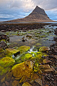 'The mountain Kirkjufell rises above the ocean near town of Grundarfjorour, Snaefellsnes Peninsula; Iceland'