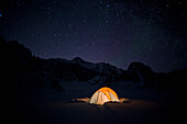 'Mountain tent on Ruth Glacier at night under star studded sky, illuminated by head lamp with the summit of Mt. McKinley in background, Denali National Park and Preserve; Alaska, United States of America'