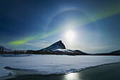 'Streak of aurora borealis over Mount Sukapak during a full moon night, Dietrich river and Brooks range; Alaska, United States of America'