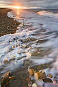Coastal landscape of waves washing upon the sandy beach along Norton Sound, Bering Sea, Nome, Arctic Alaska.