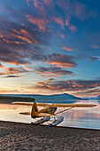 Morning sunrise over Naknek lake with a Super Cub bush plane on floats along the shore, Katmai National Park, southwest Alaska.
