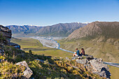 Hikers sit on rock outcrop and view the confluence of the Canning River and the Marsh Fork of the Canning river in the Arctic National Wildlife Refuge, Brooks range mountains, Alaska.