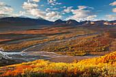 Morning sunshine falls across the Polychrome mountains highlighting the brightly colored autumn tundra, Denali National Park, Interior Alaska