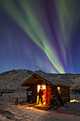 Visitors at the Caribou bluff cabin in the White Mountains National Recreation area view the northern lights overhead on a winter night.