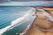 Aerial of waves rolling onto the sandy shores of Softuk bar, Gulf of Alaska, Southcentral Alaska