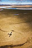 The shadow of a de Havilland beaver bush plane falls on the tundra in the Noatak Preserve, Arctic, Alaska.