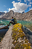 Hiker rests on rocky outcrop while enjoying the view of a clear mountain lake in the Arrigetch Peaks, Gates of the Arctic National Park, Alaska.